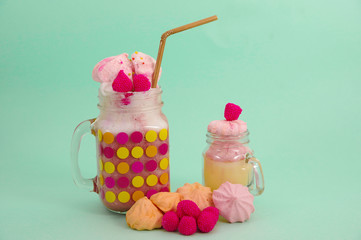 Delicious homemade extreme milkshake of strawberry in a jar, with a blackberry candy over a milk foam and a plastic straw on top, in a soft blue background