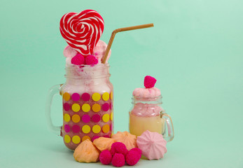 Delicious homemade extreme milkshake of strawberry in a jar, with a blackberry candy over a milk foam with a plastic straw and a pink blackberry candy with a heart candy on top, in a soft blue