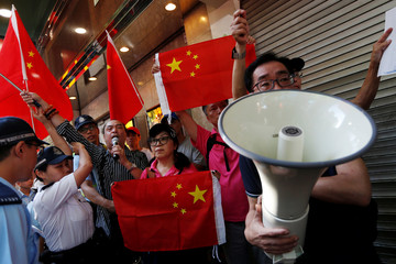 Pro-China supporters hold Chinese flags as they try to stop pro-democracy activists from protesting and demanding the release of Chinese Nobel rights activist Liu Xiaobo, during Chinese President Xi Jinping's visit, in Hong Kong