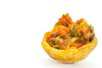 Plantain cup, made of crushed fried green plantains, filled with hogao on white background
