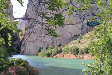 Beautiful picture postcard with the river Guadalorce passing under the bridge of the gorge of the Gaitanes in the Caminito del Rey, Malaga, Spain
