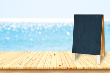 Blank blackboard on wooden terrace on the beach and sea background.