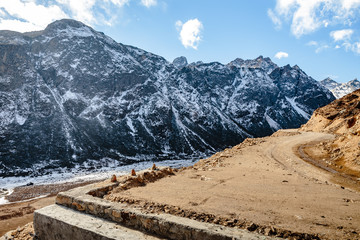Black mountain with snow on the top and yellow stone ground at Thangu and Chopta valley in winter in Lachen. North Sikkim, India.