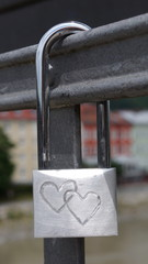 A closed or locked padlock with two hearts attached to a bridge to symbolize everlasting love between a couple.