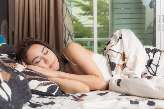 Young asia woman sleeping in her bed, she is resting with eyes closed.