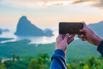 Man using smart phone take a photo mountain view,Phang Nga Bay Islands,Thailand.