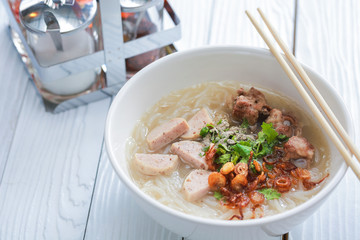 Vietnamese noodle soup on white wooden table.