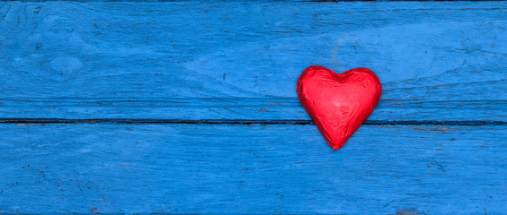 Red chocolate heart on blue wooden
