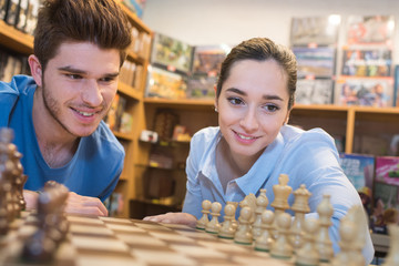 happy couple playing chess in a game store