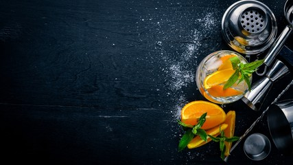 Cocktail of oranges and menthol with ice, on a black wooden surface. Top view. Free space.