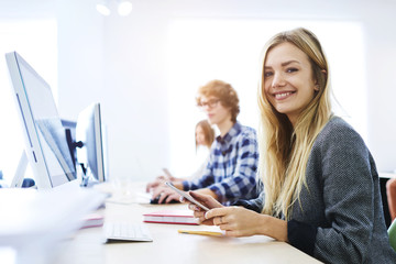 Skilled female student of business school feeling confident before writing quiz on accounting concept of marketing company sitting at lesson in good mood, smiling using technology and 5G connection