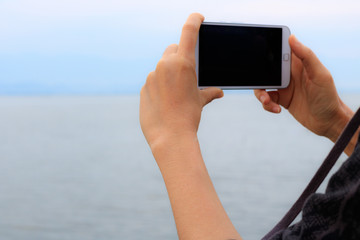 Taking photo of the lake and mountain landscape by smartphone