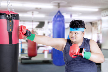 Obese man punches boxing sack
