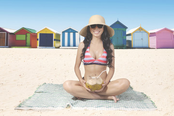 Woman drinks coconut water on beach