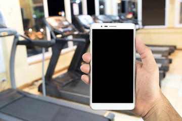 Man hand holding a smart phone in the fitness center.