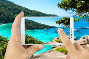 Taking photo with mobile smart phone,Beautiful sea and blue sky at Similan island,Thailand.