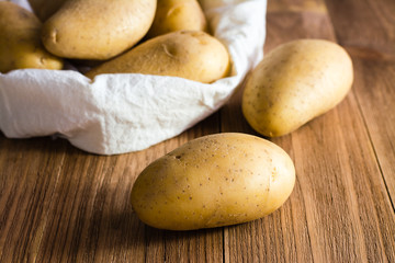 The potatoes on the background of the sack of potatoes on a wooden table
