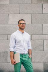 Coffee break. Confident young hipster man in glasses holding coffee cup, laptop and looking away while standing outdoors with cityscape in the background,