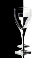 a glass of water is visible through the empty glass on black and white background