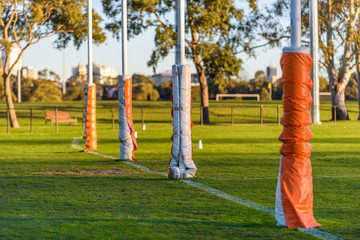 Four Australian football goal posts wrapped with protective padding at a football oval in Carlton, Melbourne, Australia