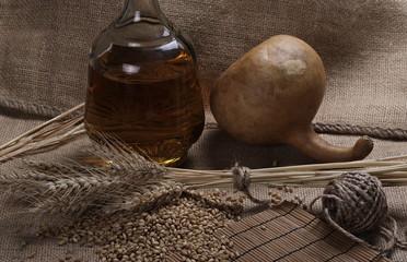 Ears of wheat, seeds, bottle of brandy and gourd on linen, jute sack