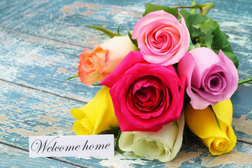 Welcome home card with colorful rose bouquet on rustic wooden surface