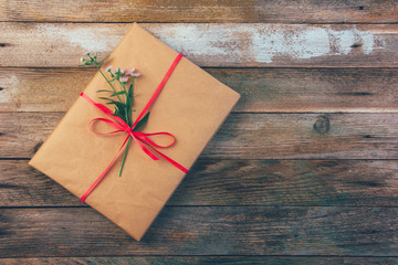 gift wrapping paper tied with a red ribbon and a Daisy flower on wooden retro grunge background with space for text, top view closeup