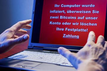 Ein Computer der mit einem Virus infiziert wurde, davor ein geschockter Benutzer