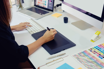 Young photographer and graphic designer at work in office.