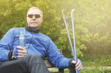 взрослый мужчина в спортивном костюме отдыхает на скамейке в парке после занятий скандинавской ходьбой