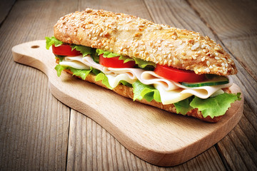 Sandwich with ham, cheese, lettuce, cucumber and tomato