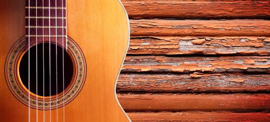 Fondo de música.Detalle de guitarra española y pared de madera.