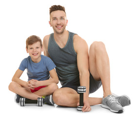 Dad and son sitting with dumbbells on white background