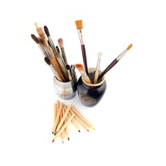 Colored pencils and brushes in various angles on a white background