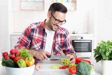 Man chopping vegetable in kitchen