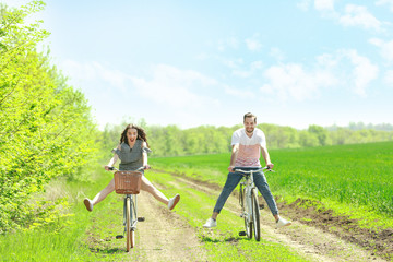 Happy young couple riding bicycles in countryside