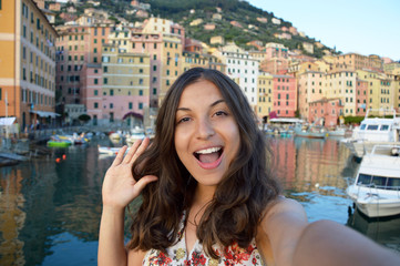 Happy young woman tanned taking selfie photo in a typical italian landscape with harbour and colorful houses for italian holidays in Liguria, Italy