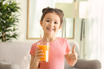 Cute little girl with glass of juice at home