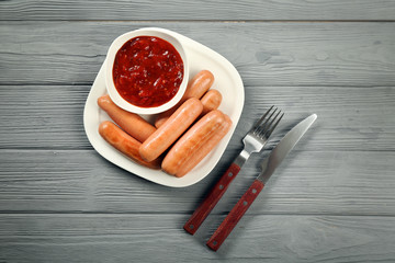 Plate with delicious grilled sausages and sauce on grey wooden table
