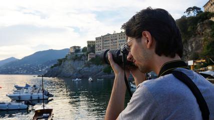 Man photographer taking photo of Camogli harbour landscape at sunset, Camogli, Liguria, Italy