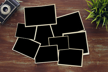 top view of blank photo frames on wooden background