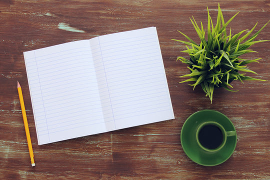 Top view of open notebbok and cup of coffee on wooden background