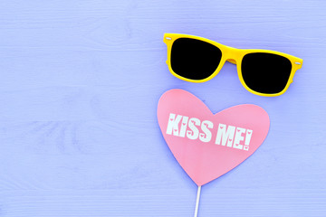 cute yellow black sunglasses and heart sign over purple wooden background