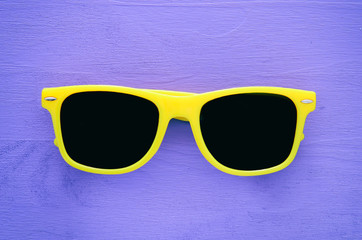 Hipster yellow sunglasses on purple wooden background