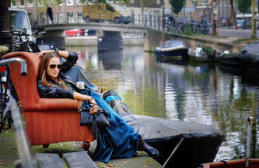 Portrait of a girl, model in an old chair on a city street next to the river. Fashion, style, beauty.