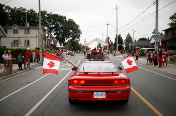 People hold Canadian flags from inside a car during the East York Toronto Canada Day parade in Toronto