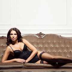 Gorgeous, beautiful and seductive woman in erotic lingerie and stockings posing on a brown sofa in vintage interior.