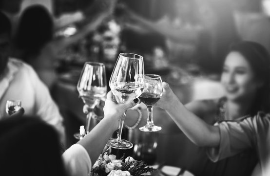 People clink glasses with wine after toast at the party
