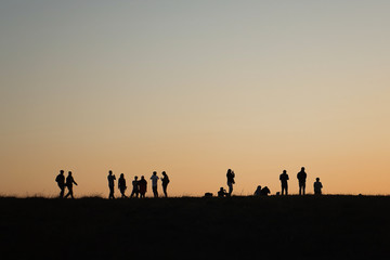 Silhouettes of hikers with backpacks enjoying sunset view