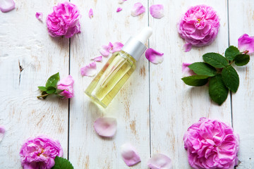 organic cosmetic with rose essence oil on white wooden background Spa treatment. Spa massage